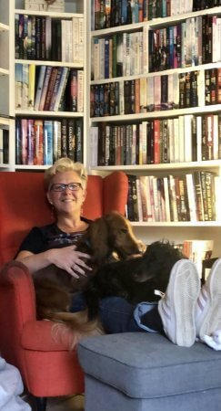 Me sitting in a red chair with my bookshelves behind me, and the dogs on my lap.